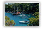 Yachts and a Turkish Gulet moored in an idyllic cove in the bay of Fethiye